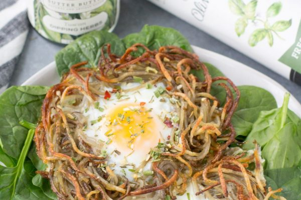 tuscan herb egg nest laid on top of spinach
